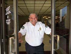 A smiling security guard opening the doors to Beverly Hospital.