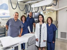 Members of the Beverly Hospital medical staff standing and smiling in a patient care room.