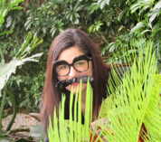 Felicia funny photo (she is hiding behind a plant wearing silly glasses)
