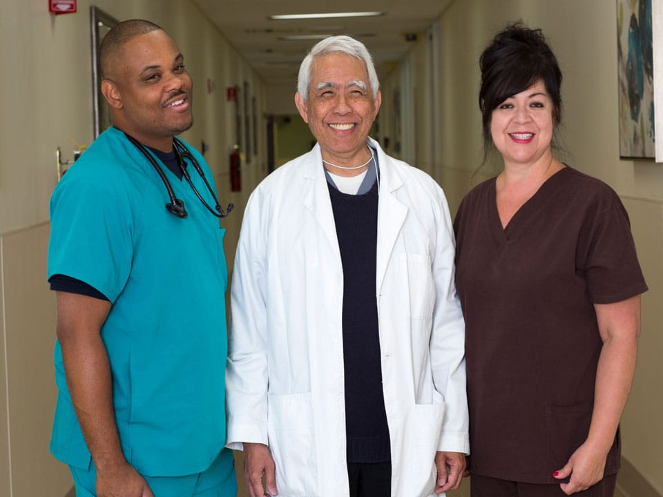Three Beverly Hospital staff members standing and smiling in the hallway.
