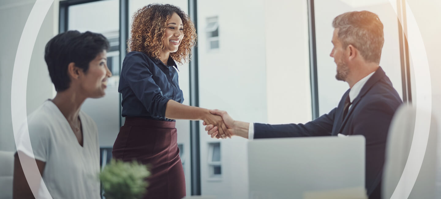 A woman shaking a man's hand in a business meeting