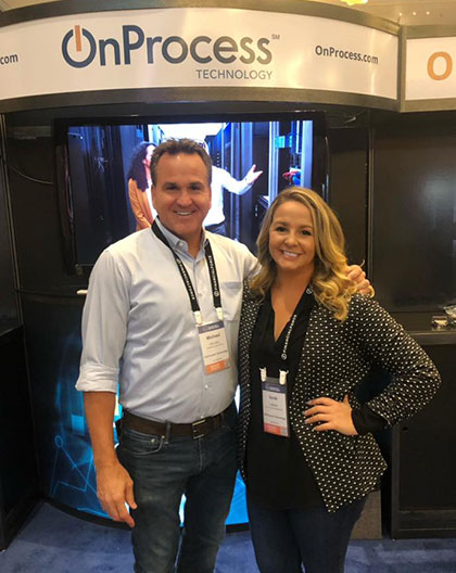 man and woman standing in front of an onprocess booth